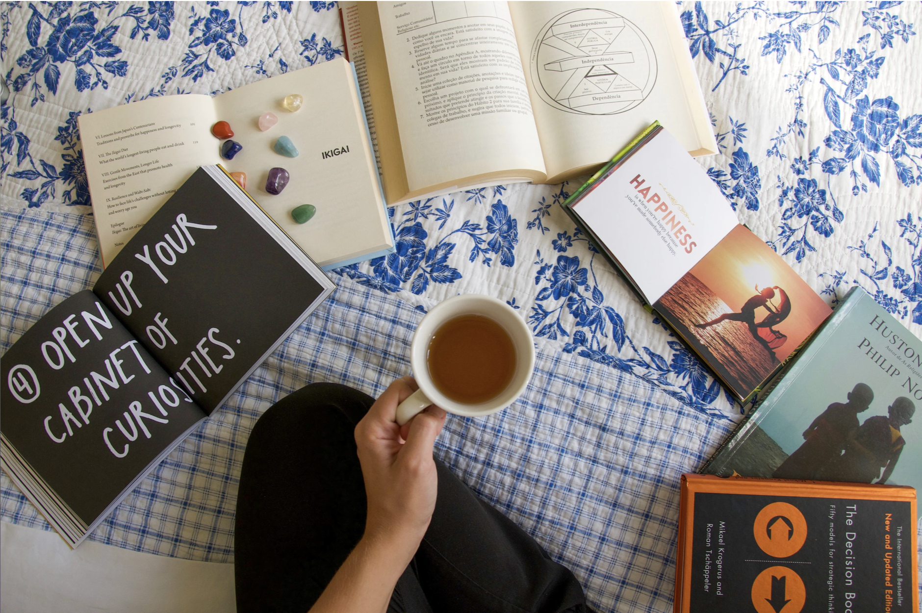 A person with a cup of tea in their hand and books on their bed