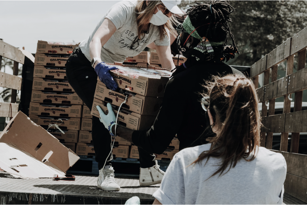 Three female volunteers unloading food from a truck